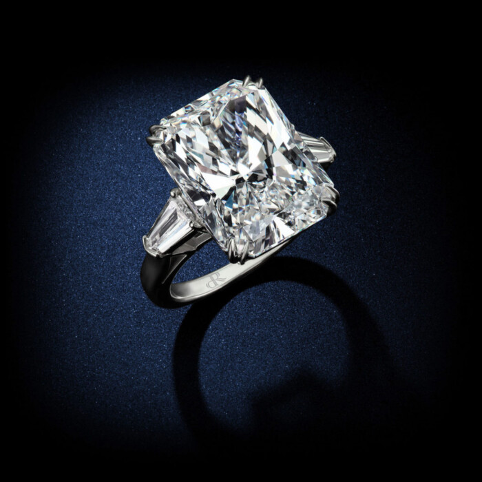 An Important 27 Radiant cut Diamond engagement ring having a color and clarity on E/VS1 set in a platinum setting and flanked by matching side stones. GIA Certified by David Rosenberg of Rosenberg Diamonds & Co. side view