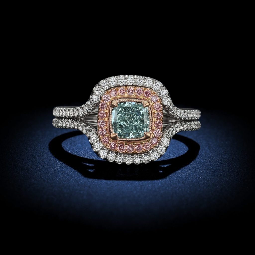 A stunning 1CT Fancy green cushion cut diamond engagement ring.GIA Certified with a platinum setting and glamorous pink and white diamond halo surrounding the center stone. By David Rosenberg of Rosenberg Diamonds & Co.
